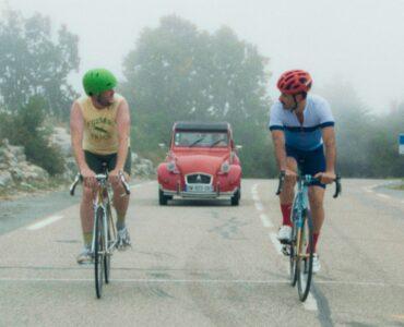 Die Freunde Mike und Kyle blicken während der Fahrradtour einander an. Hinter ihnen nähert sich ein rotes Auto.
