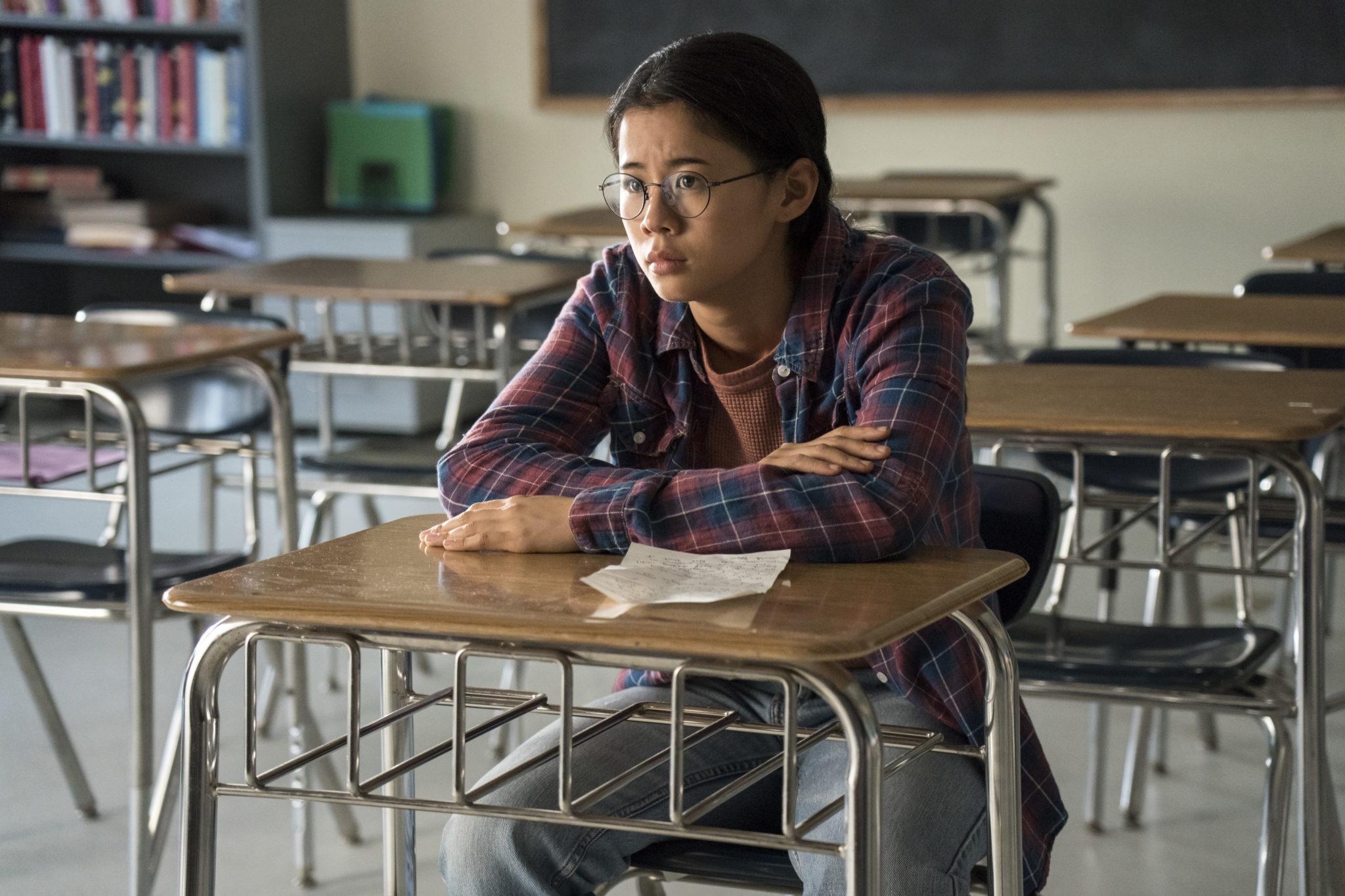 Ellie sitz allein im Klassenzimmer in Nur die halbe Geschichte