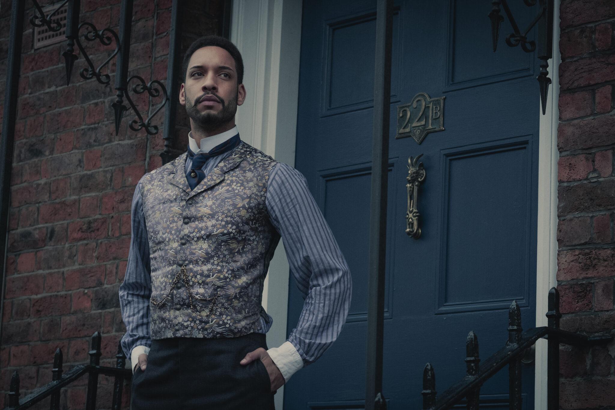 John Watson (Royce Pierreson) steht in Weste, Hemd und Krawatte gekleidet, vor der blauen Tür von Baker Street 221B