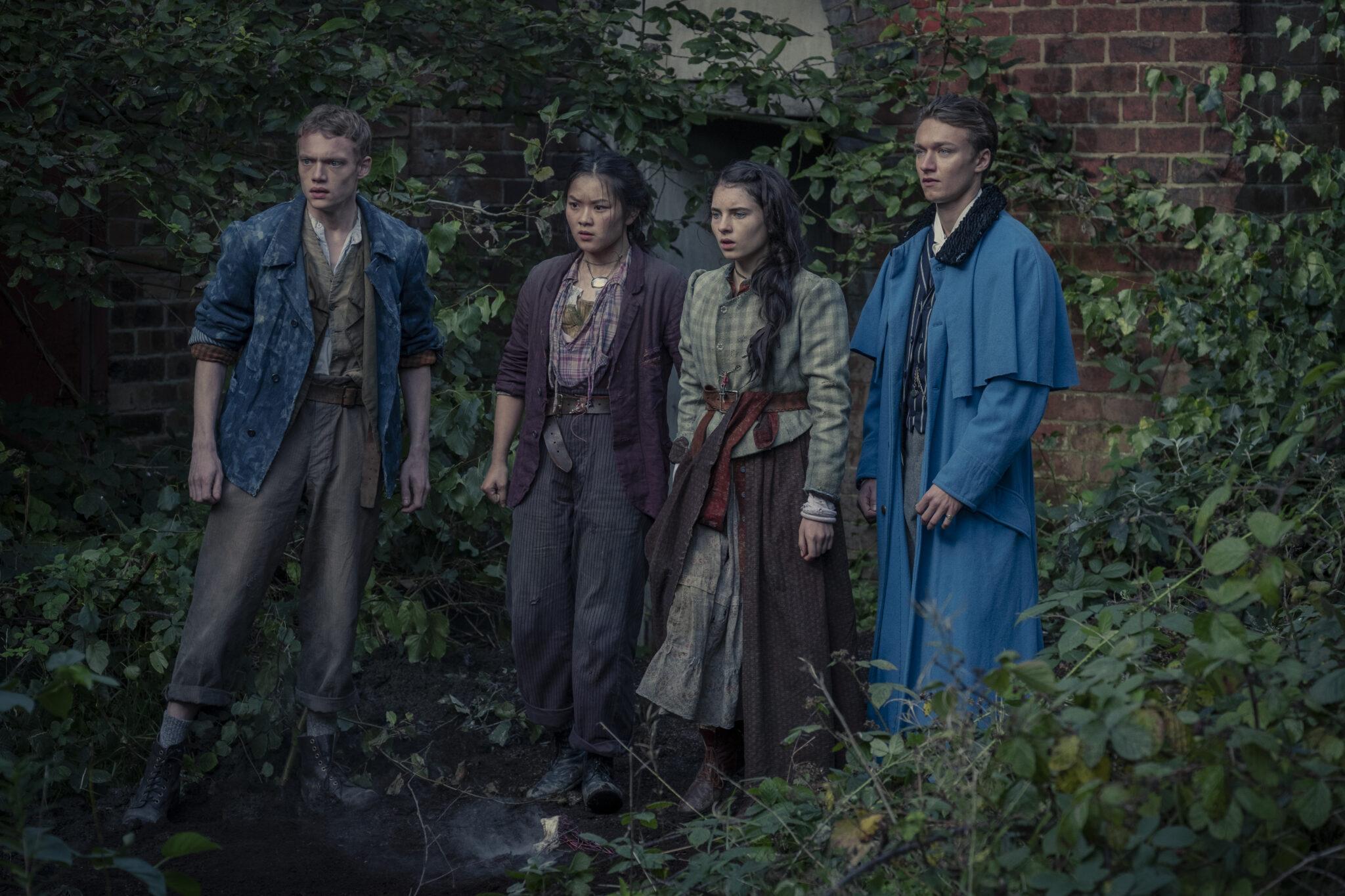 Die Bande aus der Baker Street steht vor einem eingewachsenen Mauerwerk. Von links nach rechts: Billy (Jojo Macari), Bea (Thaddea Graham), Jessie (Darci Shaw) und Leo (Harrison Osterfield)