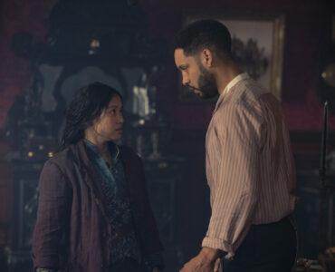 Bea (Thaddea Graham) und Watson (Royce Pierreson) führen in einem Salon eine hitzige Diskussion. Sie trägt eine braune Jacke über ihrem blauen Oberteil. Er trägt ein hautfarbenes Hemd.
