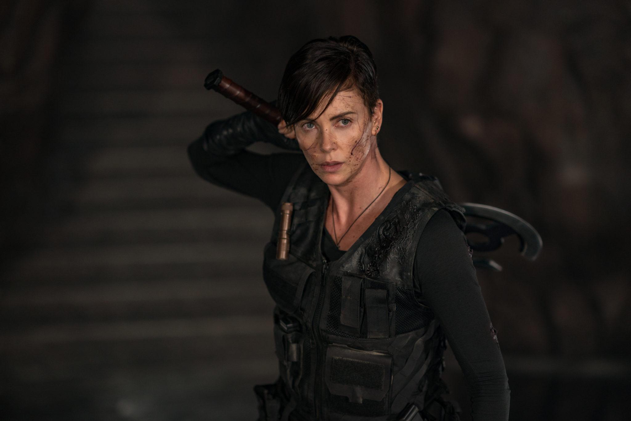 Charlize Theron als Andy, die Anführerin der Old Guard, hält mit gespanntem Blick hinter ihrem Rücken eine axtähnliche Waffe