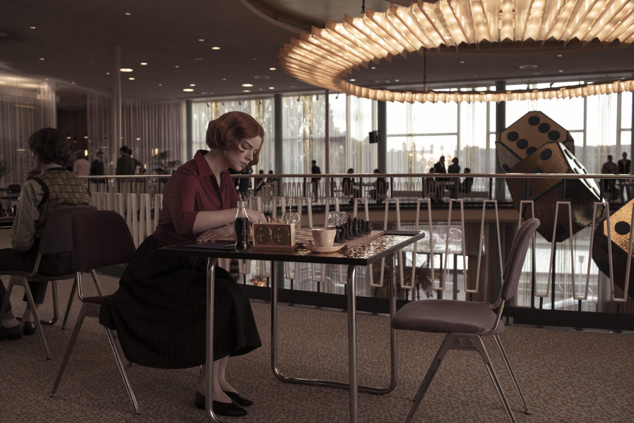Beth (Anya Taylor-Joy) studiert allein an einem Schachtisch ihr Spiel. im Hintergrund im Foyer sieht man eine große Deckenlampe, große Zierwürfel und einige schemenhafte Personen an Tischen.