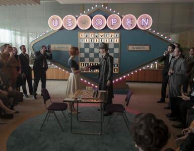 Beth schüttelt ihrem Kontrahenten vor einem Tisch die Hand. An beiden Rändern stehen Zuschauer und im Hintergrund sieht man eine grüne Anzeigetafel mit Schachmuster.