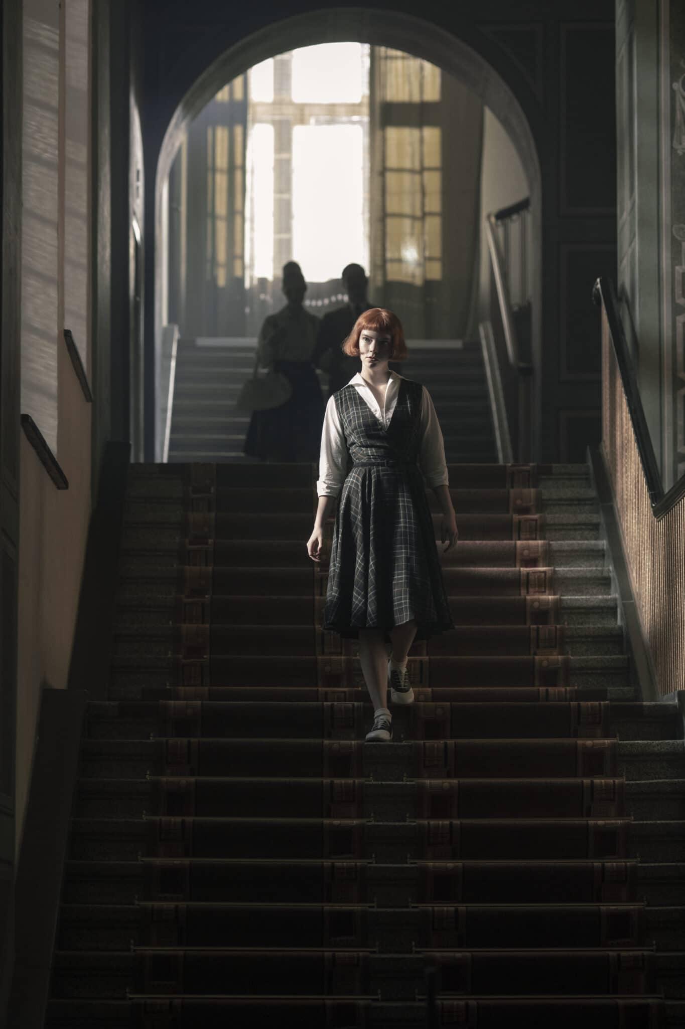 Beth (Anya Taylor-Joy) läuft eine Treppe herab. Das Treppenhaus ist spärlich beleuchtet, nur Beth selbst wird durch hereinfallendes Licht getroffen. Im Hintergrund sieht man noch ein Pärchen ebenfalls die Treppe herabsteigen.