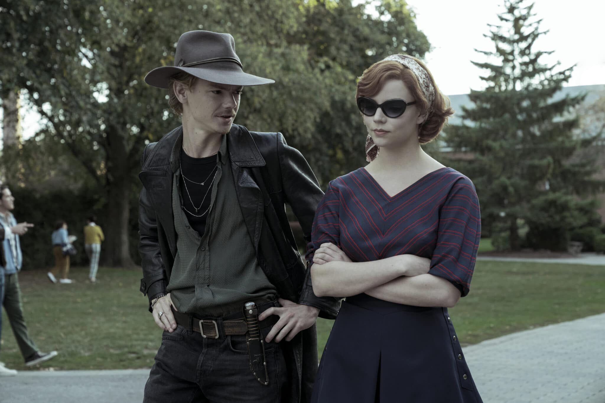 Anya Taylor-Joy als Beth Harmon mit verschränkten Armen und Sonnenbrille neben Thomas Brodie-Sangster mit Cowboyhut und dunkler Kleidung bei einem Parkspaziergang