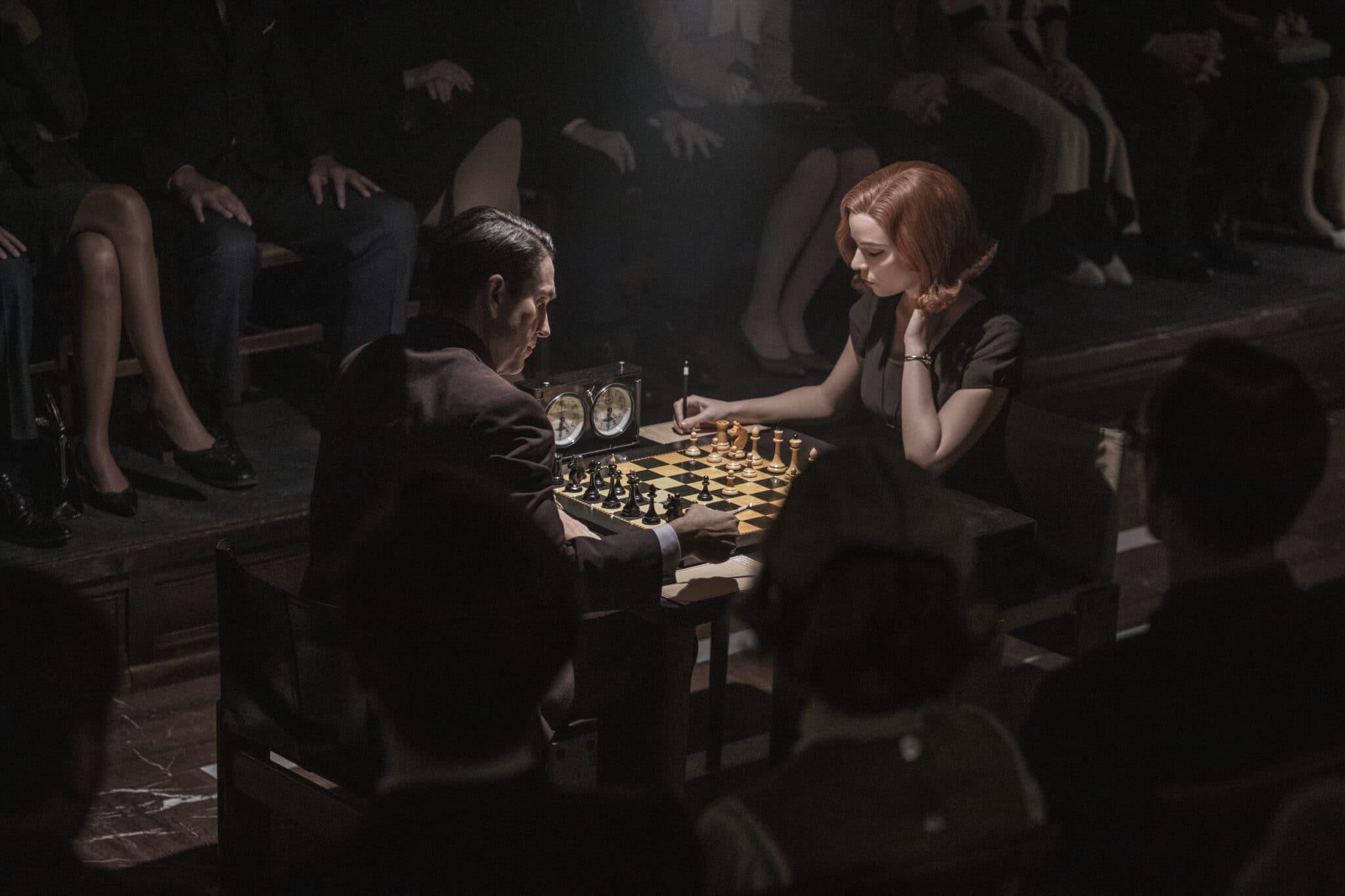 An einem beleuchteten Schachbrett sitzen Beth und Borgov. Beide blicken konzentriert auf ihre Figuren. Im Hintergrund sieht man die Beine der Zuschauer der ersten Reihe und im Vordergrund ebenfalls die Hinterköpfe von Zuschauern.