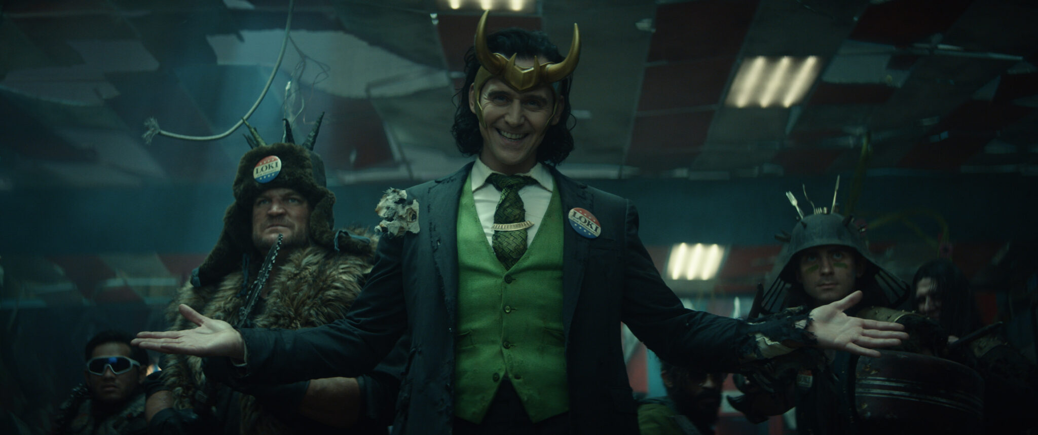 Loki (Tom Hiddlestone) mit Geweihkrone und grüner Weste unter grauem Jackett vor zwei skurrilen Figuren mit seltsamen Kopfbedeckungen.