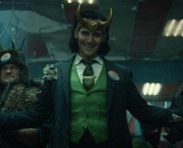Tom Hiddleston steht in Anzug und Helm vor einigen seiner wild aussehenden und bewaffneten Getreuen - Neu auf Disney+ im Juni 2021