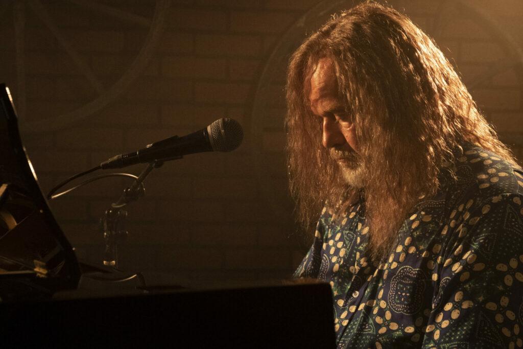 Der Protagonist sitzt in Nahaufnahme rechtsseitig in gedämmten Licht mit gesenktem Kopf vor einem Piano - The Space Between