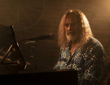 Der Protagonist sitzt in Nahaufnahme rechtsseitig in gedämmten Licht mit Blickrichtung zur Kamera vor einem Piano