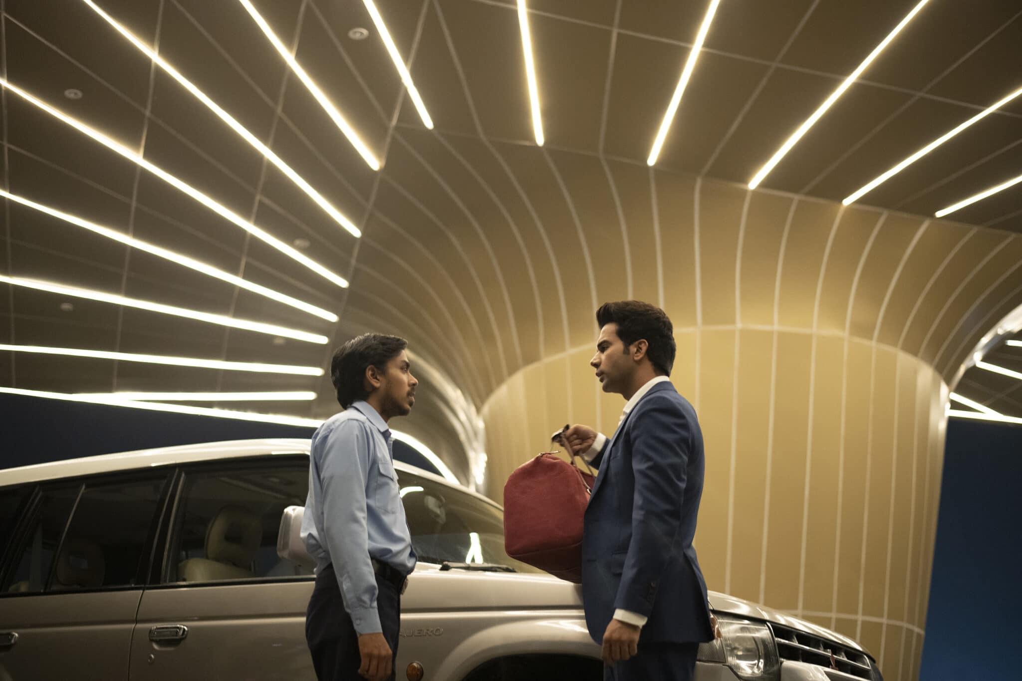 Balram steht vor dem Auto seines Herren zusammen mit diesem. Ashok hält eine rote Tasche in der rechten Hand. Über den beiden leuchten einige Neonröhren.