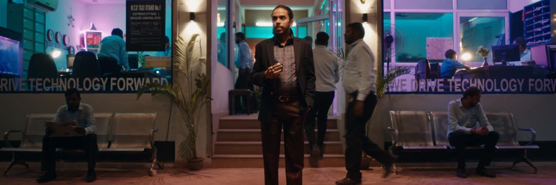 Balram steht mit einem Smartphone in der Hand vor einem neonbeleuchteten Büro. Er trägt dunkle Kleidung während Leute im Hintergrund helle Hemden tragen.