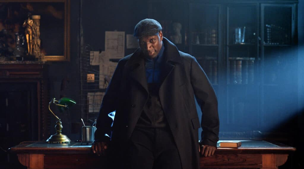 Assane Diop steht angelehnt an einem Tisch und schaut in die Kamera in Lupin.