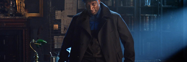 Omar Sy steht angelehnt an einem Tisch und schaut in die Kamera in Lupin.