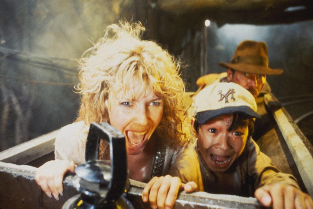 Harrison Ford, Kate Capshaw und Jonathan Ke Quan sitzen in einer Lore