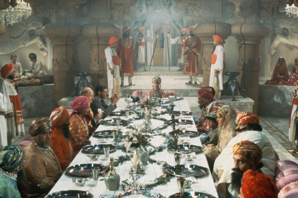 Harrison Ford, Kate Capshaw und Jonathan Ke Quan sitzen an einer reich gedeckten Tafel