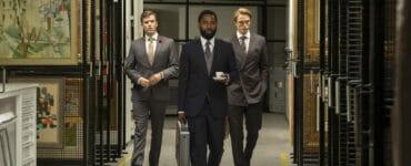 Der namenlose Agent (John David Washington) und Neil (Robert Pattinson) gehen auf dem Bild mit einem weiteren Mann durch einen Raum mit mehrere Bildern. Der Agent geht in der Mitte und hält in der linken eine weiße Tasse sowie in der rechten Hand einen silbernen Aktenkoffer. Links hinter ihm geht Neil mit den Händen in den Taschen seines Jackets, während der dritte Herr zu dessen rechten neben ihm hergeht.