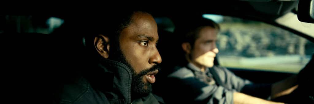 """John David Washington und Robert Pattinson spielen die beiden Agenten in """"Tenet"""". Auf dem Bild sind die beiden in Großaufnahme in einem Auto. Pattinson fährt den Wagen, während Washington auf dem Beifahrersitz ist. Beide tragen Schutzwesten und blicken sehr konzentriert nach vorne auf die Straße."""