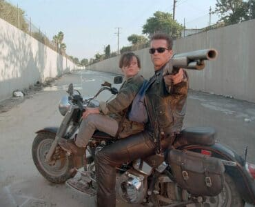"""John Connor (Edward Furlong) und der T-800-Terminator (Arnold Schwarzenegger) sitzen in """"Terminator 2"""" auf einem Motorrad. Der Terminator hat eine Schrotflinte auf die Kamera gerichtet."""