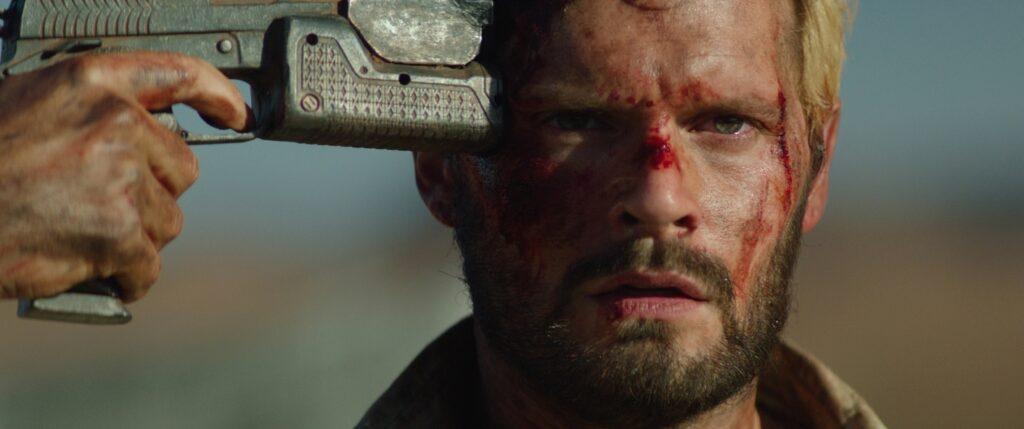 Eliott, gespielt von Paul Hamy, hält in The Last Journey Paul, gespielt von Hugo Becker, eine Waffe an die Schläfe. Im Bild zu sehen ist von Eliott aber nur seine Hand mit der Waffe.