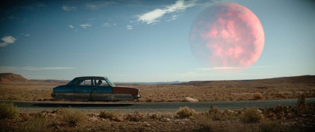 Ein räderloses Auto fliegt in The Last Journey über eine Wüstenstraße, über dem Horizont steht riesig groß und drohend der rote Mond.