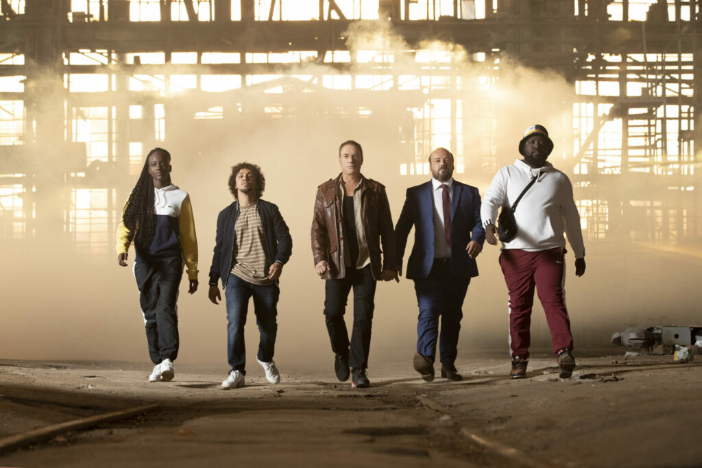 Auf dem Szenenbild aus The Last Mercenary sind eine Frau und 4 Männer zu sehen, die nebeneinander in Richtung Kamera laufen © Netflix