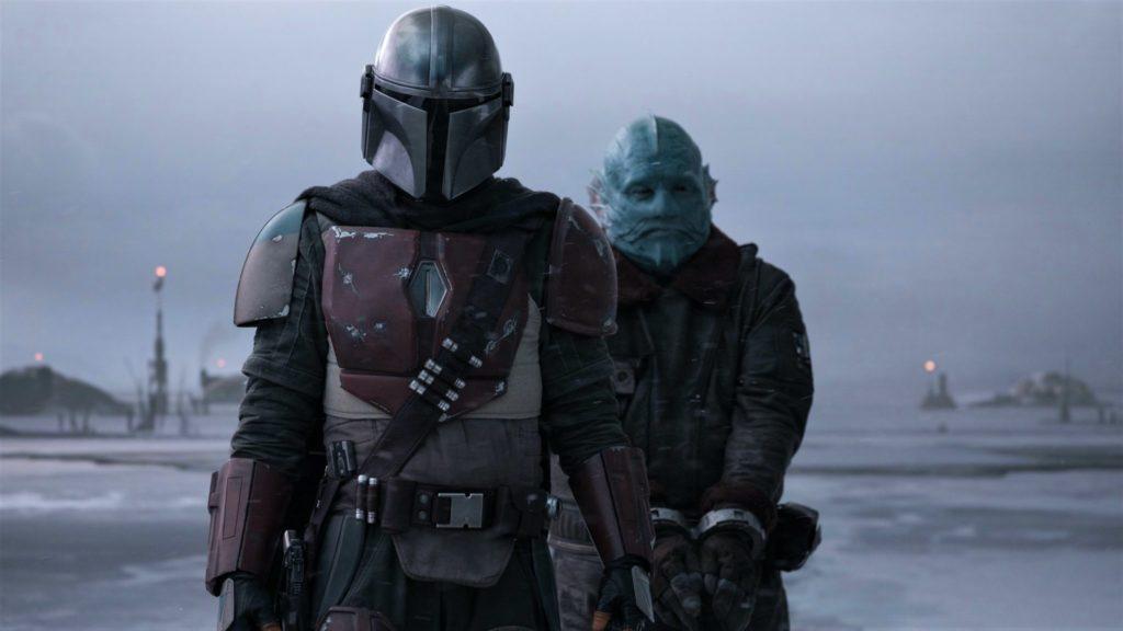 Der Mando läuft mit seinem Kopfgeld, einem blauhäutigen Alienwesen, in Richtung seines Raumschiffes.
