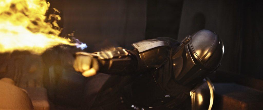 Der Mando setzt auf dem Boden liegend seinen am Handgelenk montierten Flammenwerfer ein.
