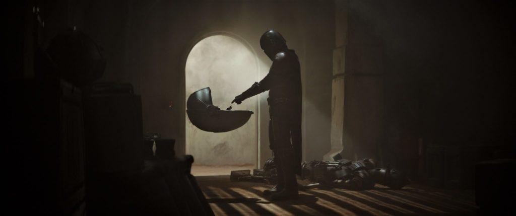 Der Mando streckt seine Hand nach dem Baby in dem fliegenden Kinderwagen aus.