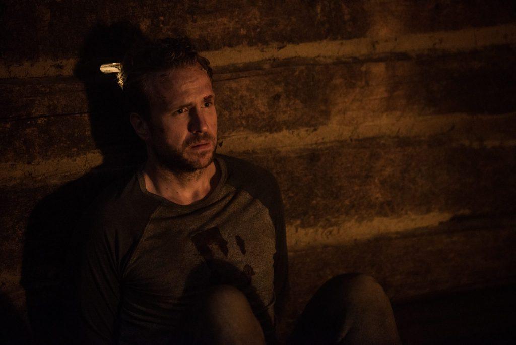 Luke (Rafe Spall) sietzt mit hoffnungslosem Blick an eine Wand gestützt in einem finsteren Raum.