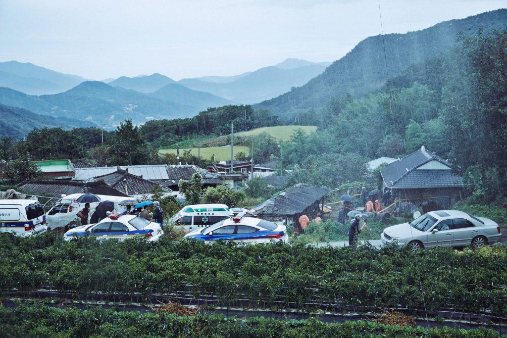 Nach einem Mordfall ist der Aufruhr in der kleinen, ländlichen Siedlung groß und vor der regenverhangenen Kulisse arbeitet ein Polizeiaufgebot an dem Fall.