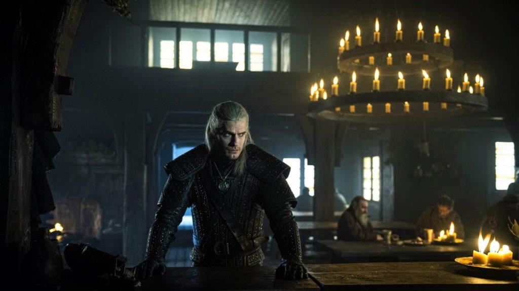 Der Hexer steht, auf seinen muskulösen Armen gestützt, vor der Theke einer heruntergekommenen, schwach beleuchteten Spelunke | The Witcher Staffel 1