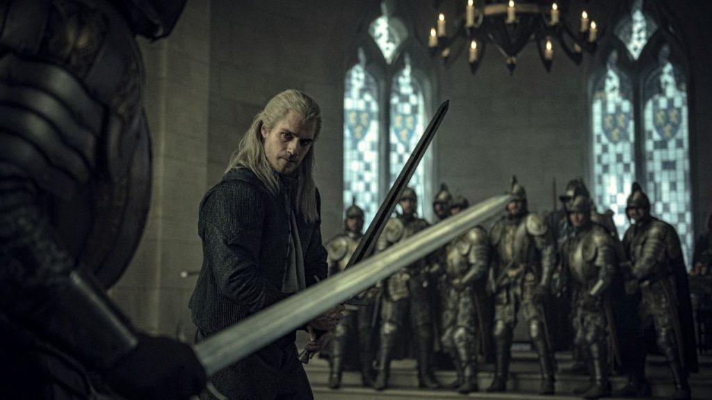 Der Hexer Geralt steht, umringt von Wachen der Königin Calanthe, mit gezogener Klinge im cintrischen Thronsaal.