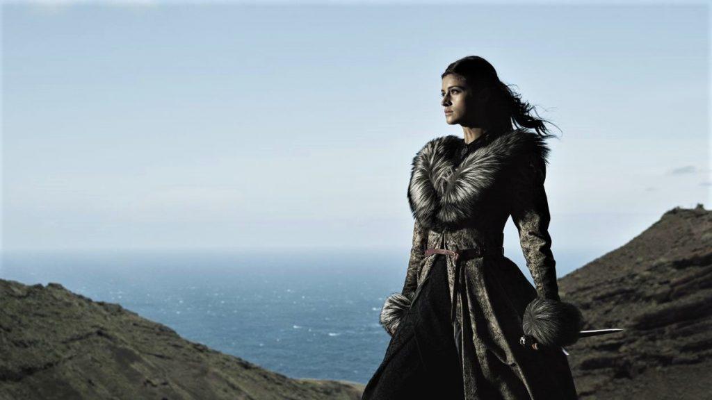 Die Zauberin Yennefer steht in The Witcher Staffel 1 in ihrem Gewand anmutig in die Ferne blickend auf einer felsigen Küste.
