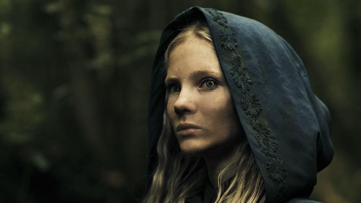 Freya Allan als Ciri in The Witcher mit blonden Haaren und schwarzer Kapuze darüber.