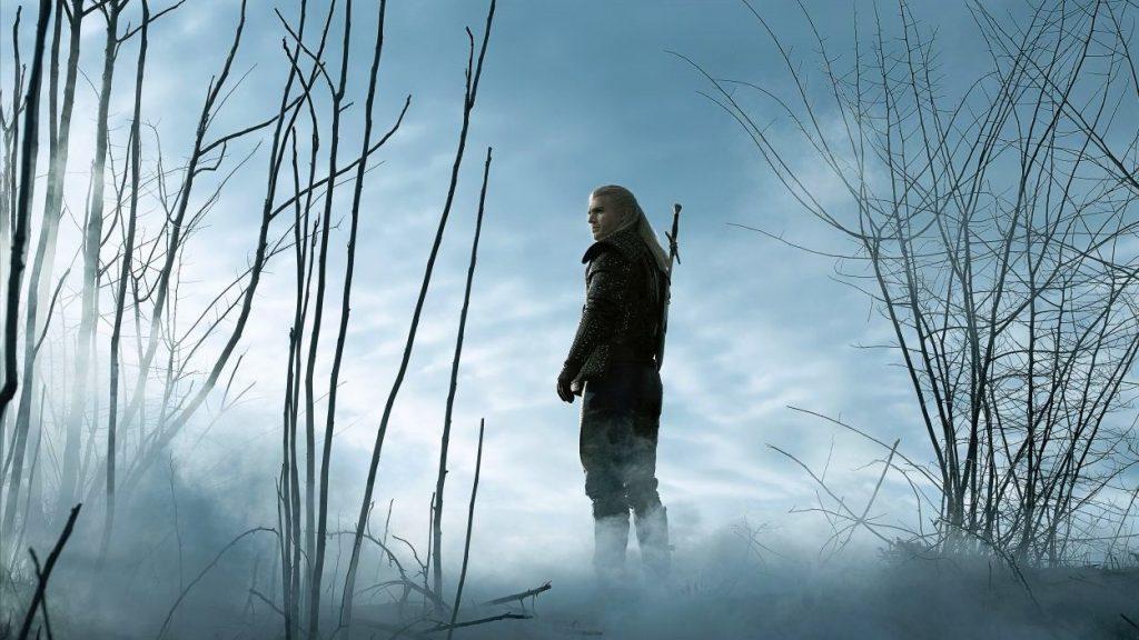 Hexer Geralt steht vor einer nebelverhangenen, sumpfigen Kulisse mit dem Schwert auf dem Rücken.
