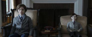 Der Junge Jude (Christopher Convery) sitzt Stuhl an Stuhl mit der Geisterpuppe Brahms in deren Anwesen.