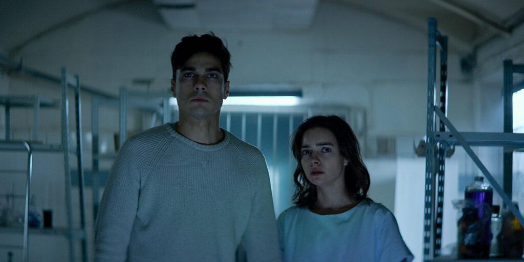 Sascha und Katja schauen sehr misstrauisch nach vorne. Sie befinden sich in einem Lager oder Krankenhaus. Das Bild wirkt sehr kühl und Katja trägt nur ein Hemd.