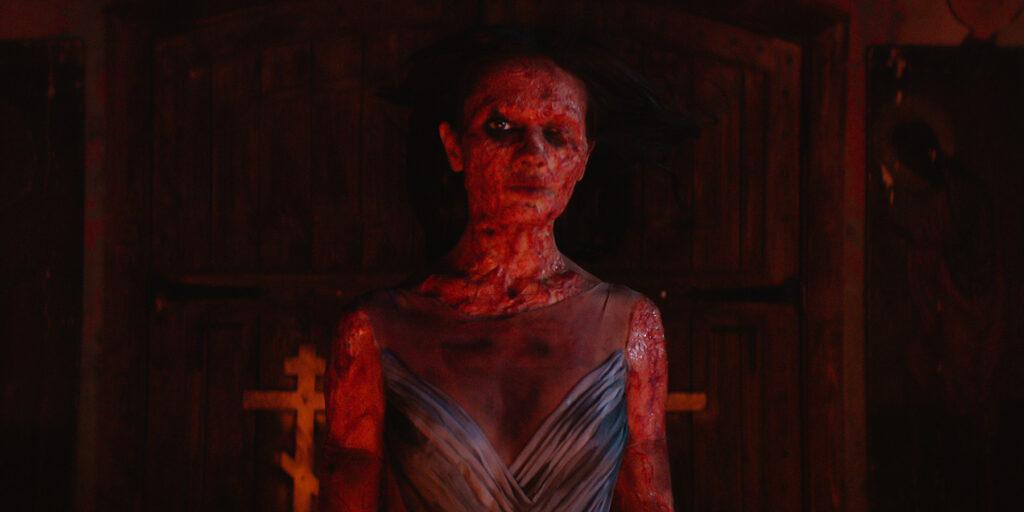 Zu sehen ist eine Person in rotem Licht. Der Körper und das Gesicht ist komplett vernarbt. Das Kleid, deutet auf eine Frau, vermutlich Saschas Ex, hin.