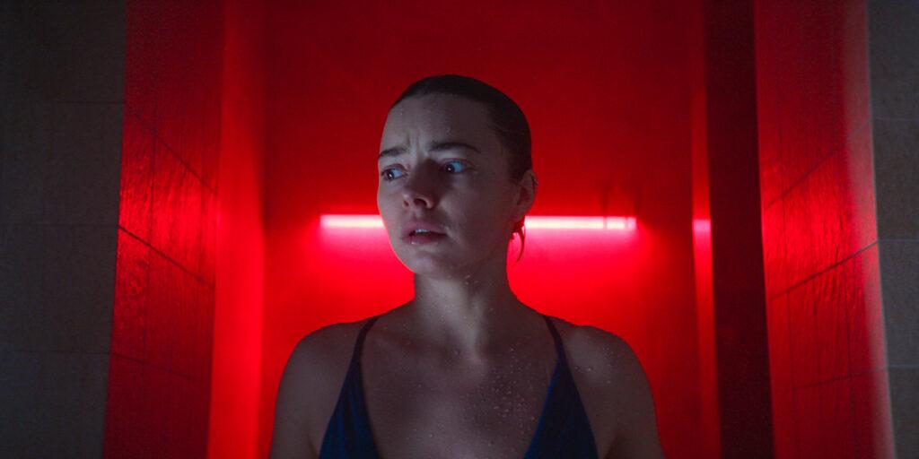 Katja befindet sich in der Mitte des Bildes und schaut sehr angsterfüllt. Das Bild ist rot beleuchtet und es sieht aus, als würde sie gerade aus der Dusche kommen.