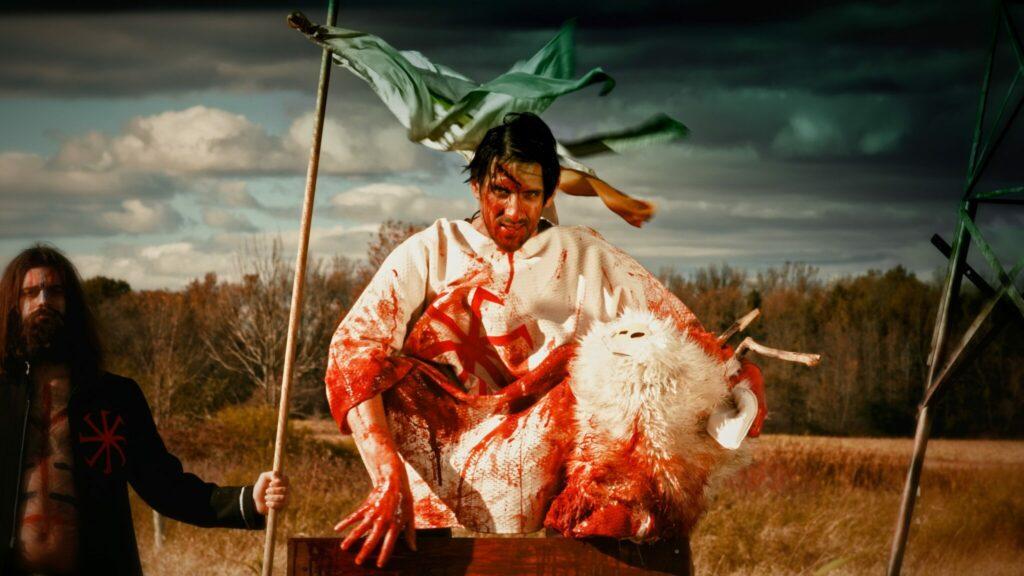 Auf einem Foto ist ein finster blickender Sektenführer in einem blugetränkten Gewand mit einem abgetrennten Tierkopf zu sehen, der offenbar zu seinen Anhängern spricht.