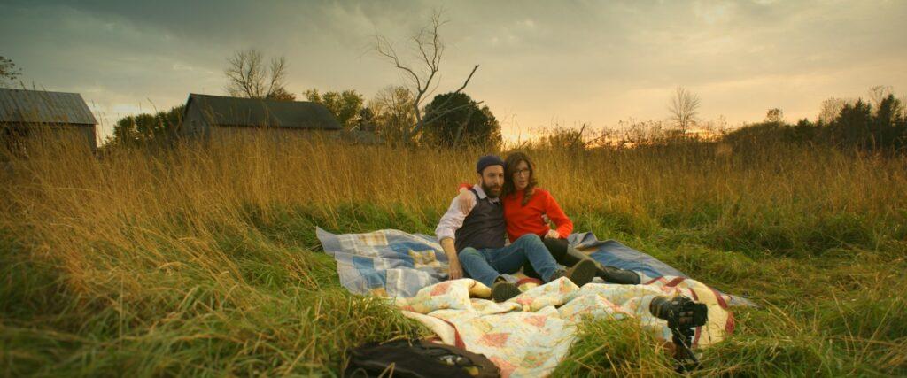 Ben, gespielt von Tim Higgins, und Lydia, gespielt von Kara Mulrooney, rekeln sich auf dem Feld, während die Kamera per Selbstauslöser klickt.