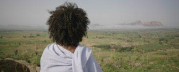 Die Kamera positioniert sich hinter Modja, die von einer erhöhten Position auf die Landschaft und die titelgebende Great Green Wall blickt.