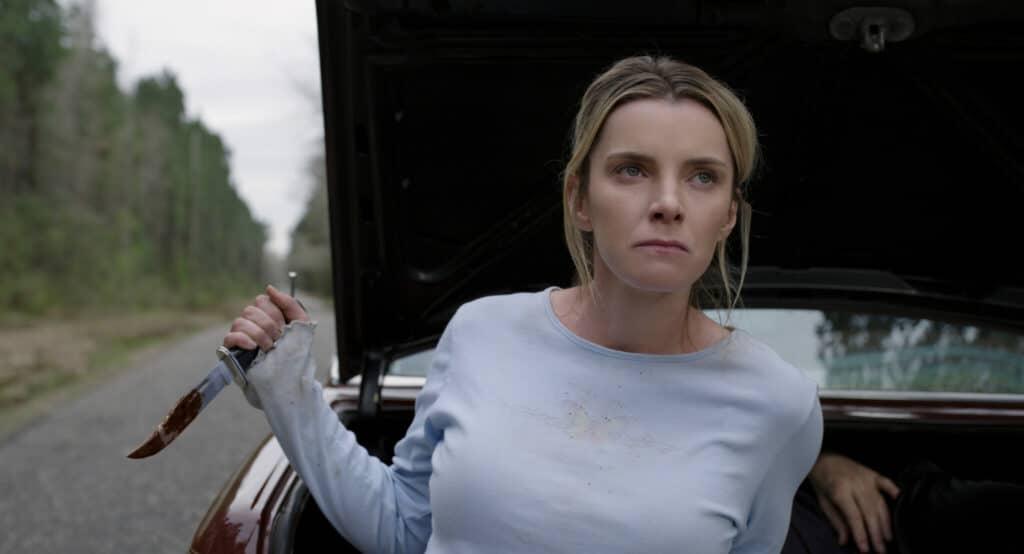 """Betty Gilpin spielt in """"The Hunt"""" die taffe Crystal. Auf dem Bild sitzt sie auf der Kante eines geöffneten Kofferraums. Im Hintergrund ist zu sehen, dass der Wagen auf einer Art Landstraße steht. Sie trägt ein blass-bläuliches Oberteil und hält in der rechten Hand ein Jagdmesser, welches Spuren von Blut aufweist. Ihr Blick ist ernst und sie verzieht keine Miene, während sie von sich aus gesehen nach links oben jemanden anschaut."""