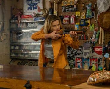 """Betty Gilpin spielt Crystal in """"The Hunt"""". Auf dem Bild trägt sie eine beige Hose, ein weißes Shirt unter einem langärmligen orangenen Hemd. Sie steht hinter einem Holztresen und hält eine Flinte mit kurzen Lauf in beiden Händen. Im Hintergrund sind verschiedene handwerkliche Gegenstände und Zubehörteile. Ihr Blick ist ernst und fokussiert, während sie auf etwas zielt."""