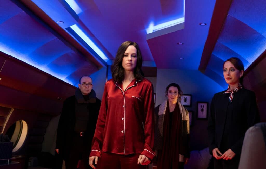 """Hilary Swank spielt in """"The Hunt"""" die rätselhafte Anführerin der Menschenjäger. Auf dem Bild steht sie im roten seiden Pyjama inmitten eines Luxus-Jets. Zu ihrer rechten steht eine Stewardess, hinter ihr ein Mann mit lichtem Haar und Brille, sowie eine Frau mit braunen Haaren und einem Schal.Swank blickt mit Verachtung nach unten zu Boden, während die anderen drei erleichtert dreinblicken."""