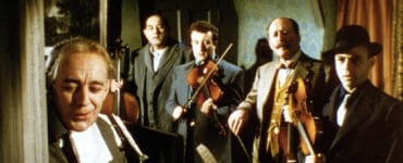 Die fünf Kriminellen um Professor Marcus (Alec Guinness) geben sich in Ladykillers gegenüber Mrs. Wilberforce (Katie Johnson) als Streicherquintett aus. Sie stehen stramm im gemieteten Zimmer und halten die Instrumente als Tarnung in der Hand.