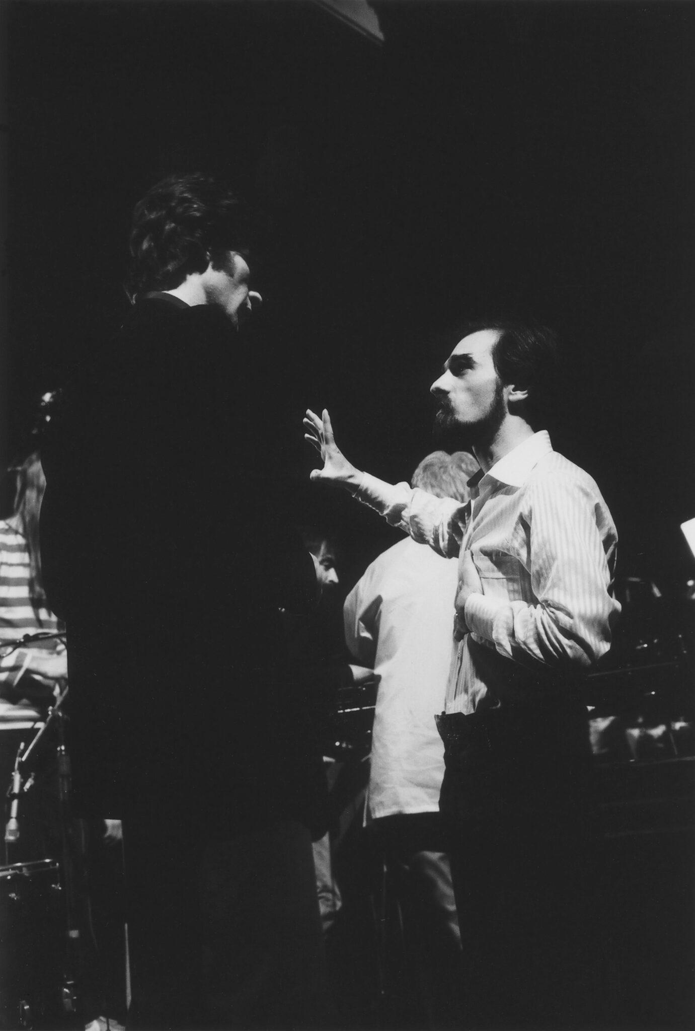Das Schwarz-Weiß-Bild zeigt Robbie Robertson und Martin Scorsese hinter den Kulissen zu The Last Waltz in einem Gespräch vertieft.