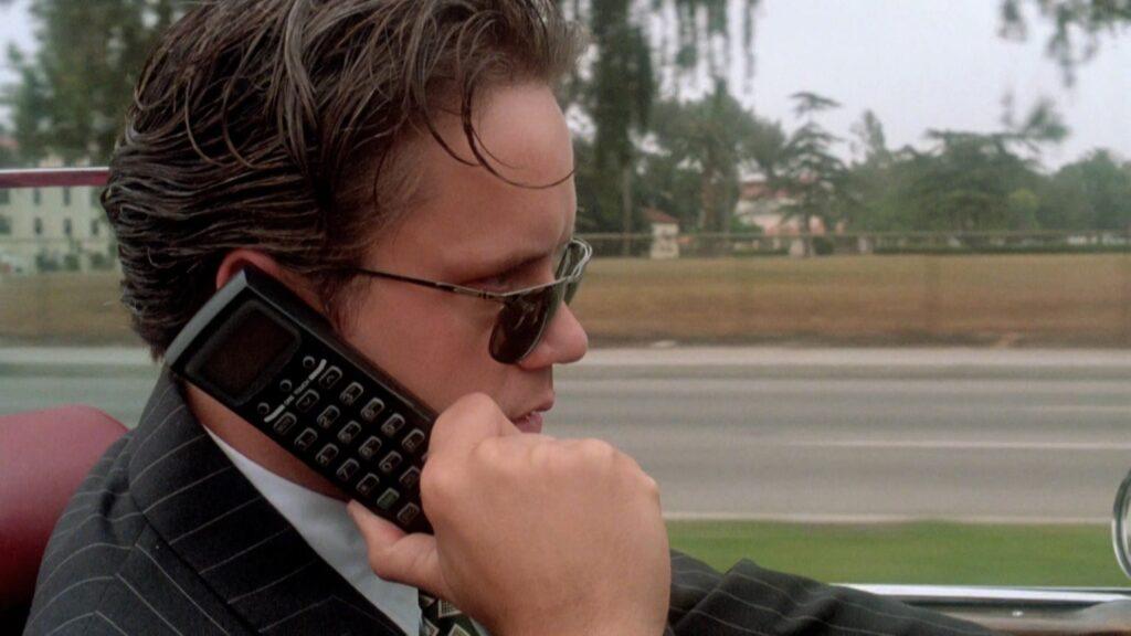 Griffin Mill (Tim Robbins) telefoniert, während er Auto fährt, mit den Studioverantwortlichen. Er hält sich sein Handy an das rechte Ohr und blickt durch seine Sonnenbrille hindurch in Fahrtrichtung.